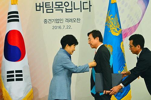 박근혜 대통령으로 부터 금탑산업훈장을 수훈받고 있는 다이소 박정부 회장