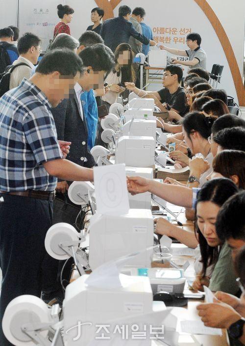 6·13 지방선거 사전투표 첫날인 8일 오전 서울 서울역에 마련된 사전투표소에서 시민들이 투표용지를 받고 있다 [사진: 김용진 기자]