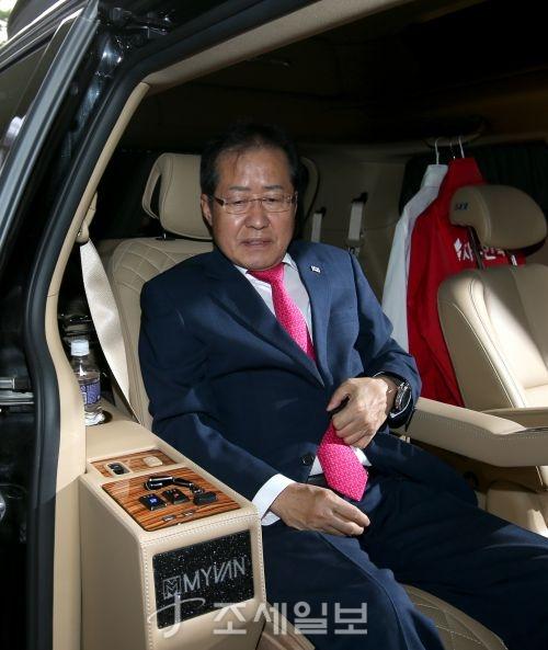 대표직 사퇴를 밝힌 뒤 당사에서 나와 차량에 올라탄 홍준표 자유한국당 대표. 그의 뒷편으로 붉은색과 흰색의 한국당 선거복이 걸려있다. (사진=김용진 기자)