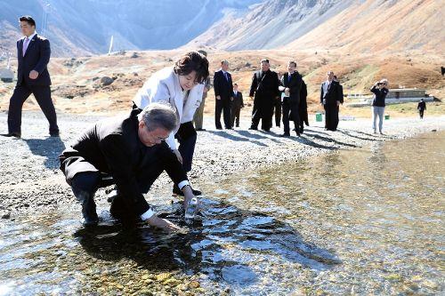 문재인 대통령이 20일 오전 김정은 국무위원장과 백두산 천지를 산책하던 중 천지 물을 준비한 물병에 담고 있다.(사진=평양사진공동취재단)