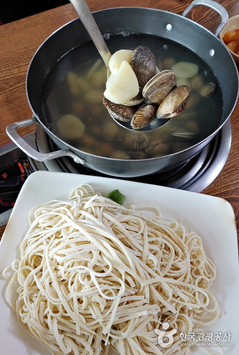 싱싱한 바지락을 끓여 건져 먹은 뒤 국물에 칼국수를 넣는다.
