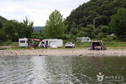 캠핑카와 텐트에서 캠핑을 즐기는 사람들