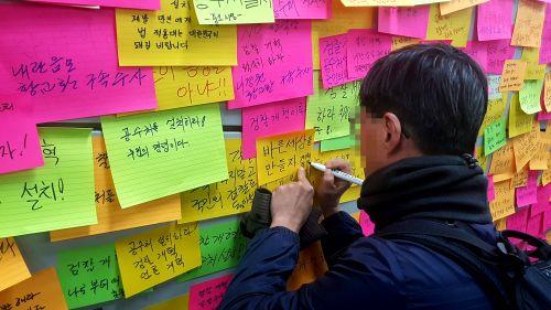 서울 여의도 인근에서 26일 열린 제11차 검찰개혁 촛불 문화제가 끝난 뒤 한 시민이 여의도역 벽면에 검찰 개혁을 촉구하는 쪽지를 붙이고 있다.